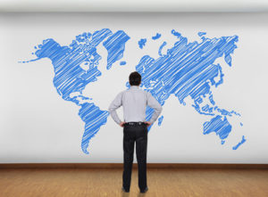 businessman in office looking at wall with world map